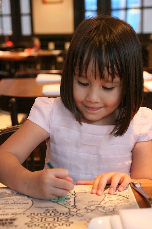 Jolie happily coloring the activity panels for kids at Halia