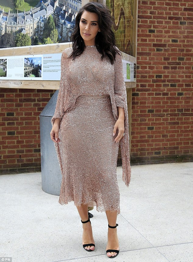 Standing tall: Kim smoldered in front of the camera in her form fitting pink dress