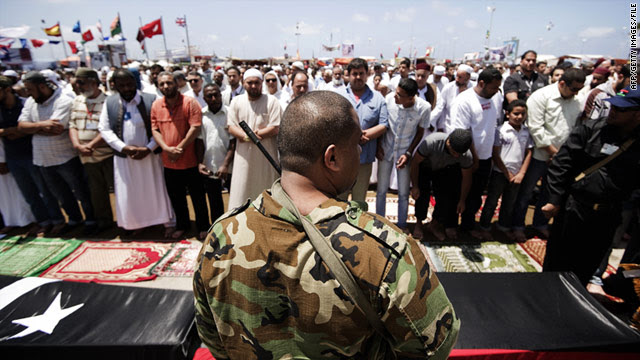 A file photo of armed Libyan rebels standinjg next to coffins in Benghazi on June 10, 2011.