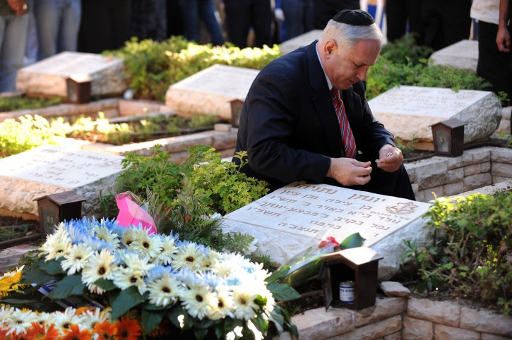 FILE - Israel's Prime Minister Benjamin Netanyahu sits next to the grave of his brother Yoni, as he lits a candle, during a memorial ceremony to Yoni Netanyahu in the military cemetery in Mt. Hertzel, Jerusalem, Israel, June 28, 2009.  EPA/AHIKAM SERI / POOL