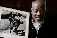 South African photographer Sam Nzima poses with the classic picture he took of Hector Pieterson being carried after martyrdom during the first day of the Soweto rebellion of 1976. by Pan-African News Wire File Photos