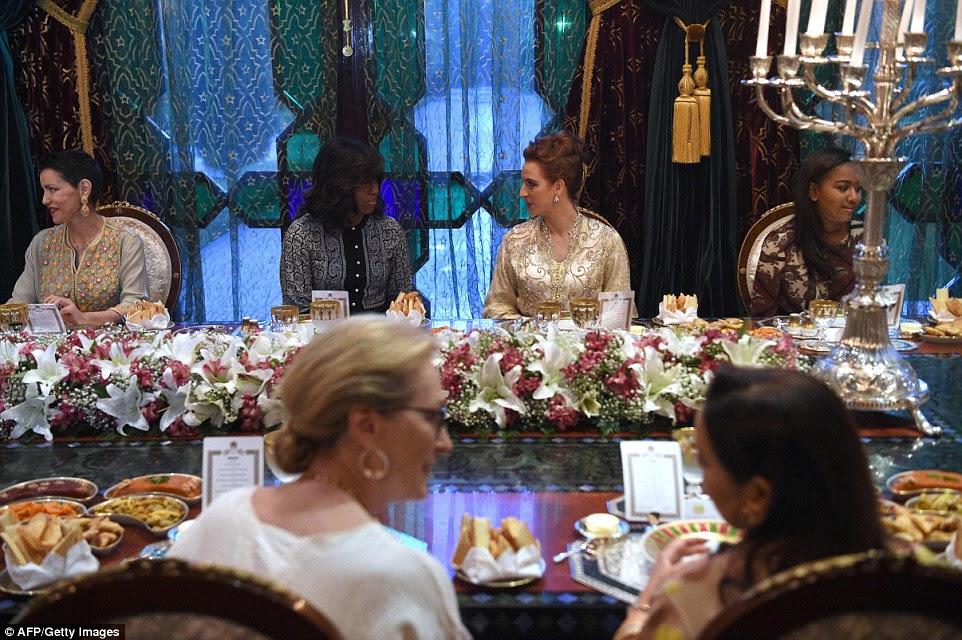 Uma peça central floral enorme decorados mesa como os convidados dobrado em iguarias tradicionais marroquinas durante a refeição