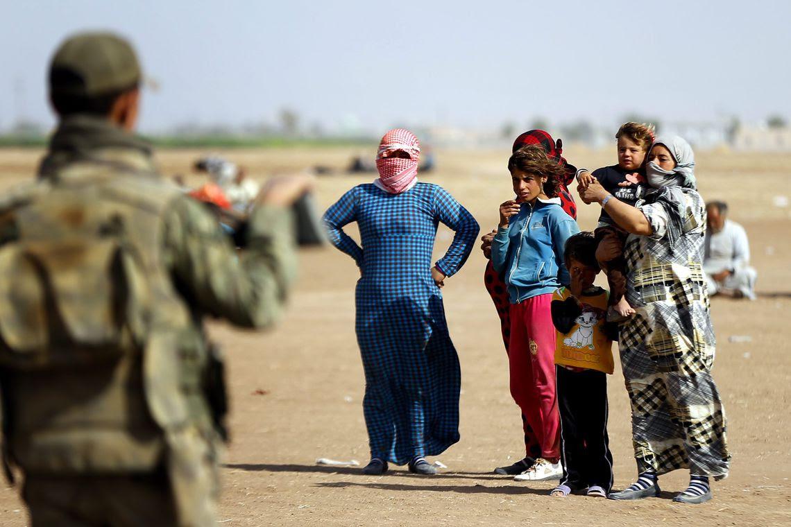Refugiados sírios aguardam na fronteira com a Turquia para fugir dos ataques do Estado Islâmico (EPA/Sedat Suna/Agência Lusa)