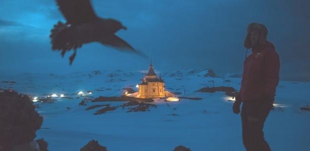 Cientista caminha com a igreja ortodoxa russa ao fundo, em área de bases da Antártida