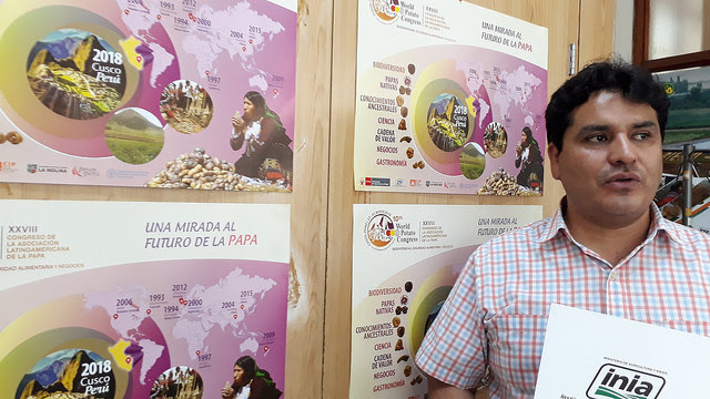 Jesús Caldas, director of Management of the National Institute of Agricultural Innovation (INIA), the Peruvian state entity that leads the Organising Committee of the 10th World Potato Congress, is photographed in his office next to the promotional posters for the event that will take place in the city of Cuzco in May. Credit: Mariela Jara / IPS
