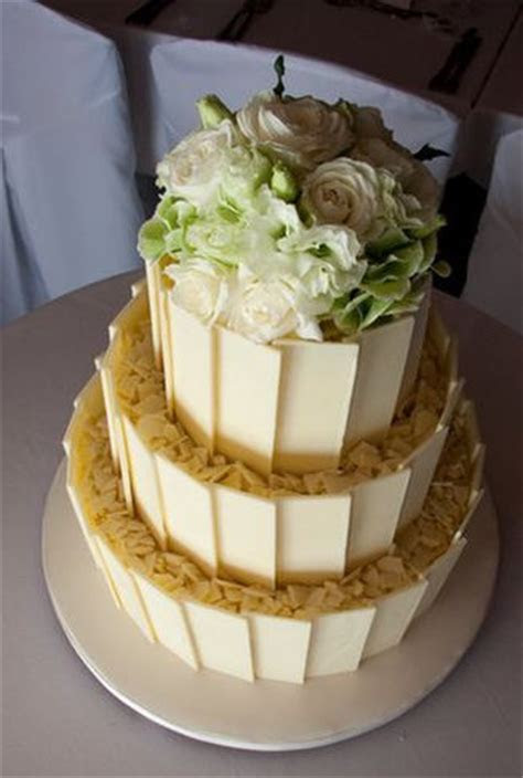 Three tier white chocolate cake topped with white roses