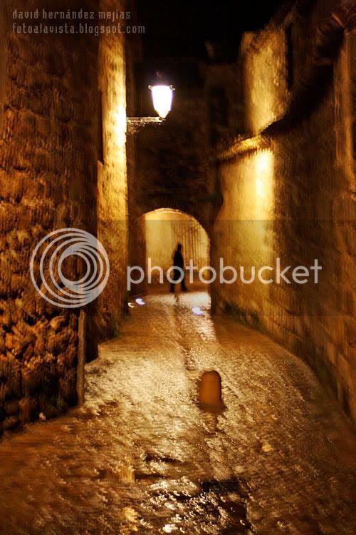 Silueta humana caminante bajo un arco vista callejeando bajo la lluvia entre los muros del centro histórico de Baeza, Jaén