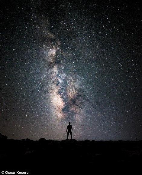 """As imagens assombrosas de Oscar Keserci mostram silhuetas de árvores solitárias, praias desertas, estradas vazias e figuras individuais iluminadas pela explosão dramática de milhões de estrelas acima.  Esta imagem intitulada a criação do deus, foi disparada em uma visita do verão a Rhodes.  O Sr. Keserci disse que """"quis encontrar o lugar o mais escuro na ilha"""" viajou assim com os amigos à montanha dos Attaviros, o ponto o mais elevado de Rhode para conseguir este tiro."""