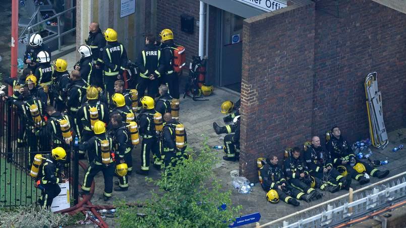 Des pompiers prennent un temps de repos, près du bâtiment, mercredi matin. Les 250 agents mobilisés ont oeuvré toute la nuit contre le feu.