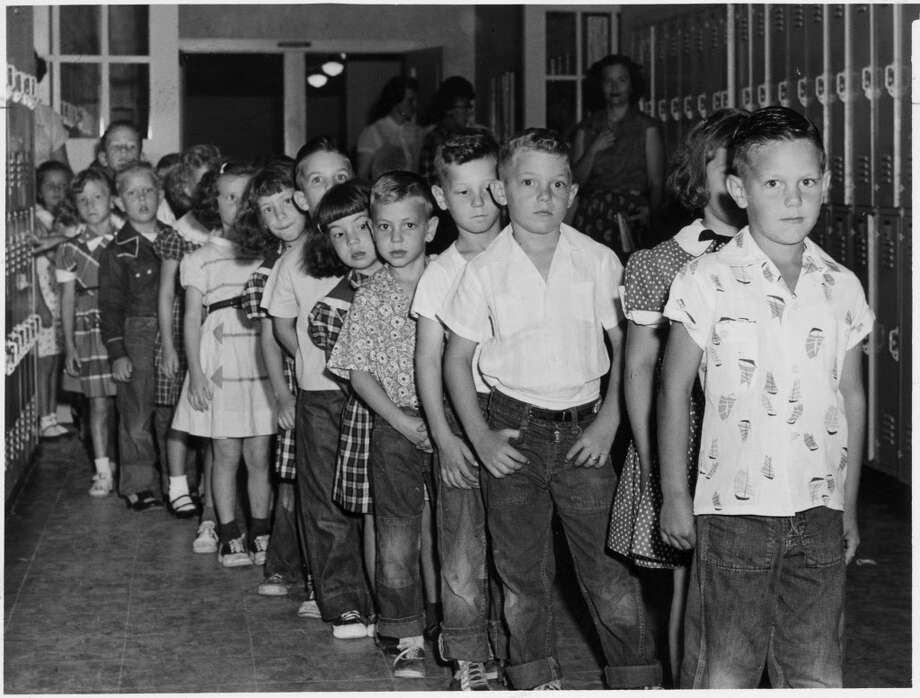 Schoolchildren await Salk vaccine shots at Houston's Hohl Elementary in 1955. Harris County's polio crisis was unmatched in Texas. / Houston Chronicle