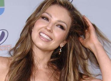 thalia sonriendo acomodandose el largo cabello