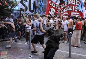 Demonstrators clash with police in front of the Casa de Tucuman in Buenos Aires, on December 12, 2012 during a protest against the sentence that allowed the release of 13 indicted in cases of forced disappearance of women, prostitution and involvement in the case of Marta Veron, disappeared in the province of Tucuman ten years ago (AFP Photo)