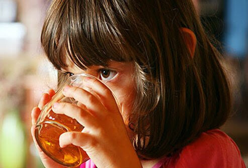 A young girl drinking a cup of hot tea.