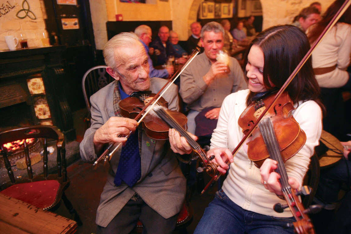This undated image provided by the Northern Ireland Tourism Board shows performers playing traditional Irish music at Kelly's Cellars in Belfast, Northern Ireland. It'll cost you to have a pint, of course, but you can enjoy the music for free. It's one of a number of places around Belfast to experience good conversation and music. (AP Photo/NITB)