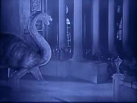 In the foreground, a dinosaur.  In the background, actors. From the 1925's The Lost World.