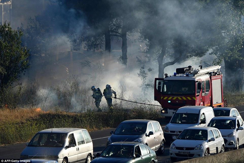 Os motoristas dirige na estrada ao lado de bombeiros pulverização extintor de incêndio, como parte de uma tentativa de lutar contra um incêndio que se espalhou perto Vitrolles, no sul da França