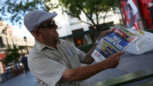 Tomas Colon reads a newspaper with a Spanish headline that reads, 'more sacrifices,' a day after the speech Puerto Rican Governor Alejandro Garcia Padilla gave regarding the government's $72 billion debt on June 30, 2015, in San Juan, Puerto Rico.