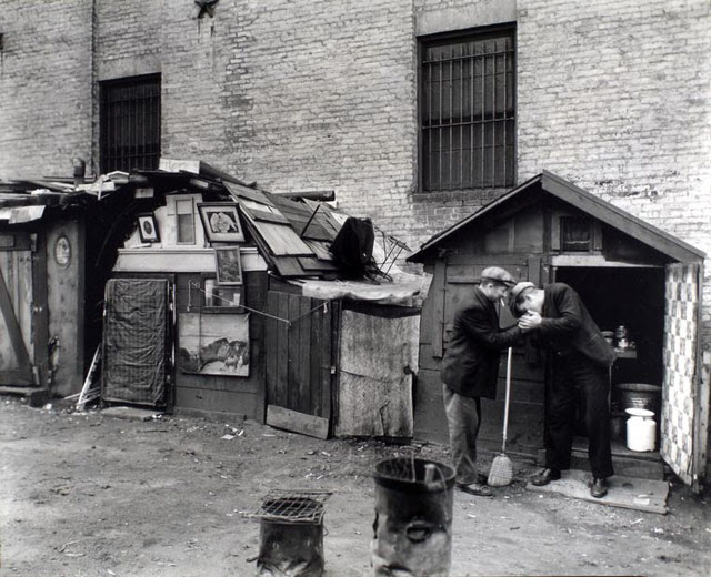 Huts and unemployed, West Houston and Mercer Street, Manhattan. Men share a light in front of hut with open door, milk can and washtub inside, hut to left has pictures in frames adorning the outside of it.
