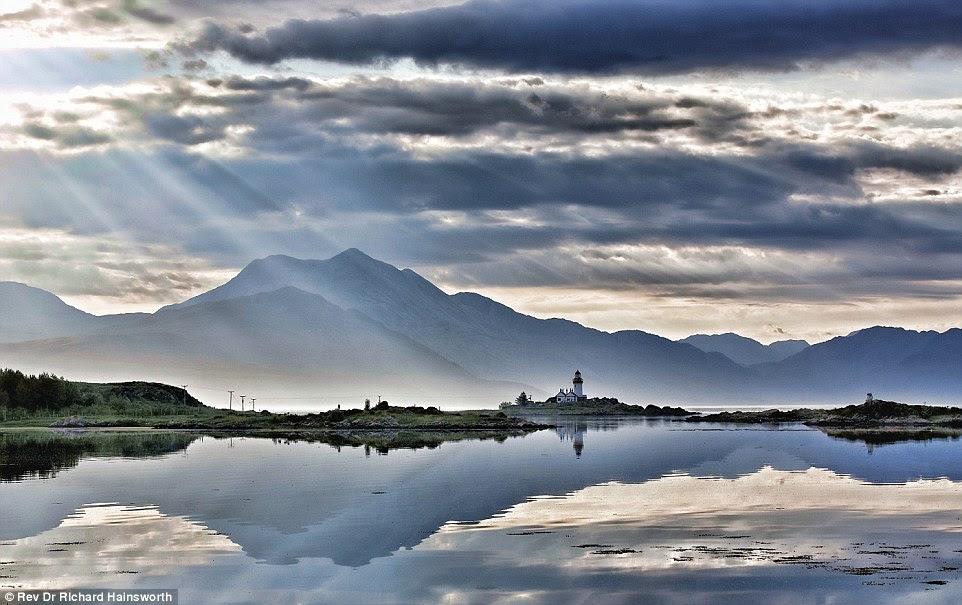 A serenidade da ilha Farol Ornsay na Escócia é retratado como feixes de luz pausa das nuvens nesta imagem pelo Rev Dr. Richard Hainsworth