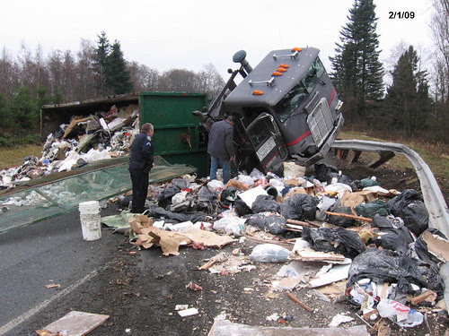 Garbage truck spills its load