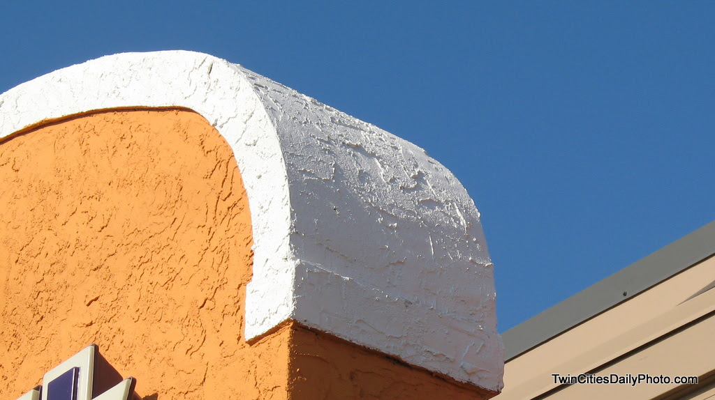 The top corner of the entrance to a very well known fast food joint. The contrasting colors caught my eye while I was waiting in line.