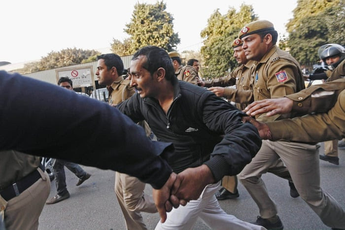 Policemen run to escort taxi driver Shiv Kumar Yadav outside court in New Delhi, India. The Uber driver is on trial for allegedly raping a female passenger