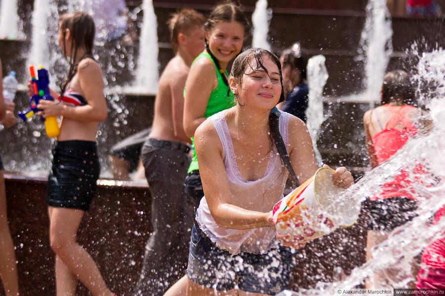 Девушка в мокрой белой майке рядом с фонтаном