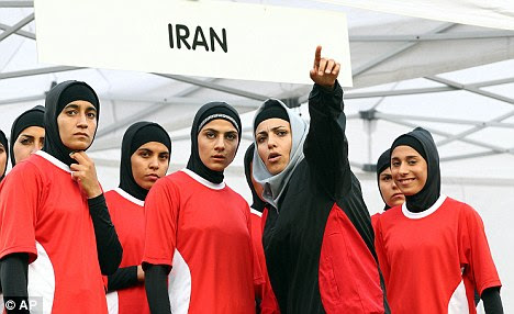 Female coach Fatemeh Moolai, with arm raised, talks to her players during the women's rugby sevens tournament where the Iran team appeared in Europe for the first time