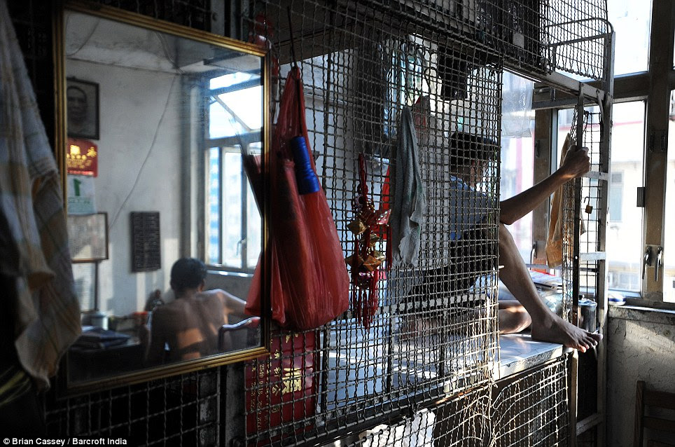 Getting some work done: Tang Man Wai, 60 (right) looks out of the window as his roommate sits at a desk, a rare luxury in the filthy, dank cage rooms