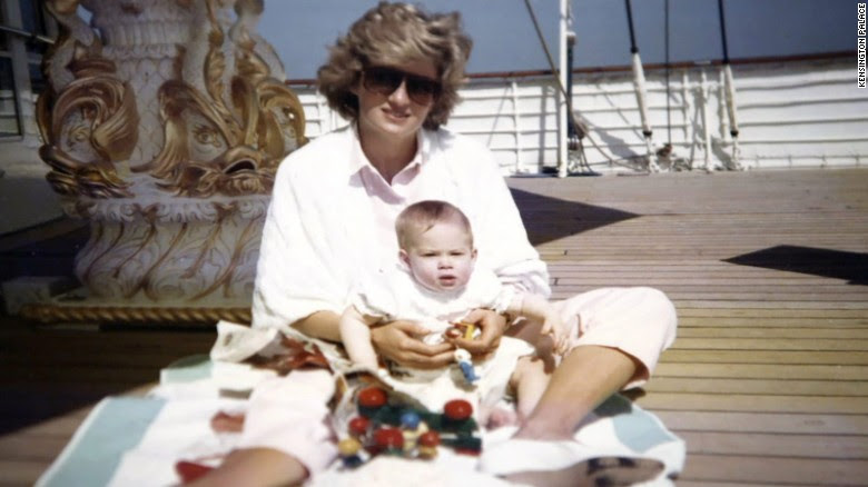 Princess Diana holds a baby Prince Harry in her arms as she sits on board the Royal Yacht Brittania.
