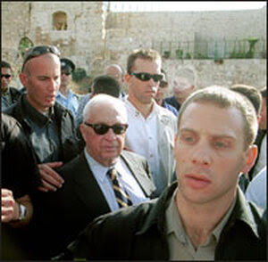 Sharon, surrounded by security personnel, leaves the Temple Mount in Jerusalem.