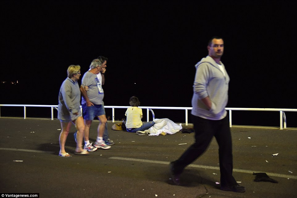 Tragédia: Uma família de turistas olhar para uma mulher em amarelo enquanto se senta ao lado do corpo de um ente querido, morto no ataque terrorista