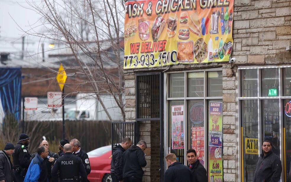 Oficiais de polícia de Chicago investigam cena onde quatro pessoas foram por um atirador em um restaurante (Foto: Joshua Lott / Getty Images / AFP Photo)