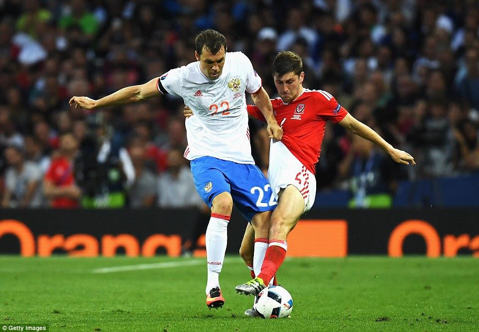 Russia's star strikerArtem Dzyuba (left) pulls Wales' Spurs left back Ben Davies' shorts as he battles for the ball