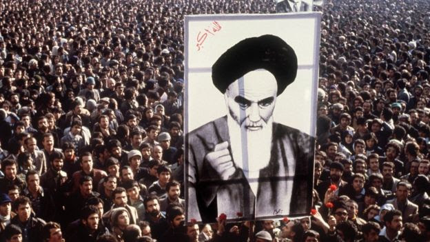 Iranian protestors hold a up a poster of Ayatollah Khomeini during a demonstration in Tehran (January 1979)