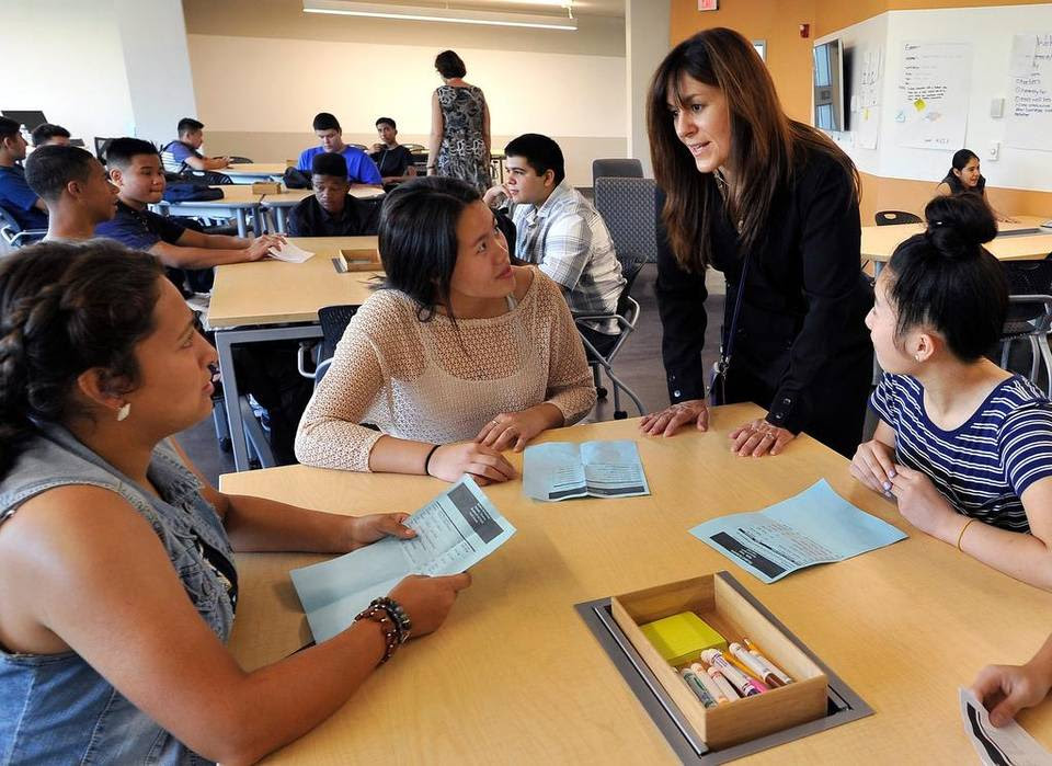 History teacher Sue Gularte talks with new students, from left, Daniella Guerra, Hnub Lee and Katie Yang, on the first day of classes at Fresno's new Phillip J. Patiño School of Entrepreneurship. State education officials estimate districts will have to fill nearly 21,500 open teaching slots this school year.