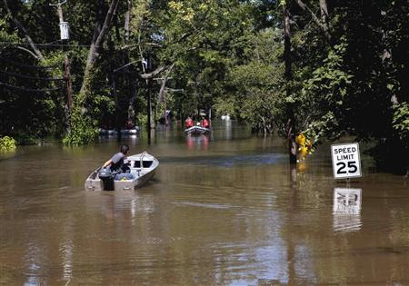 A man manoeuvres his boat near a rescue team through a flood caused by Hurricane Irene in Wayne, New Jersey