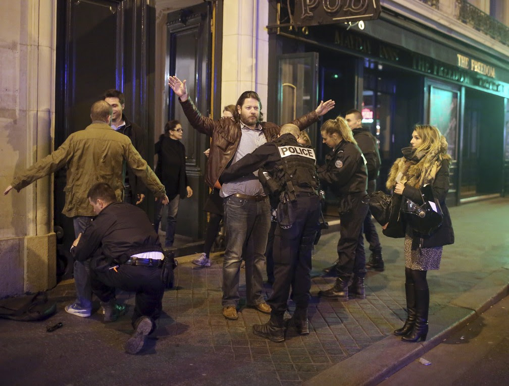 Policiais revistam pessoas após tiroteio na avenida Champs-Élysées, em Paris (Foto: AP Photo/Thibault Camus)