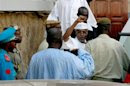 Former Chad president Hissene Habre rises his fist as he leaves a court in Dakar