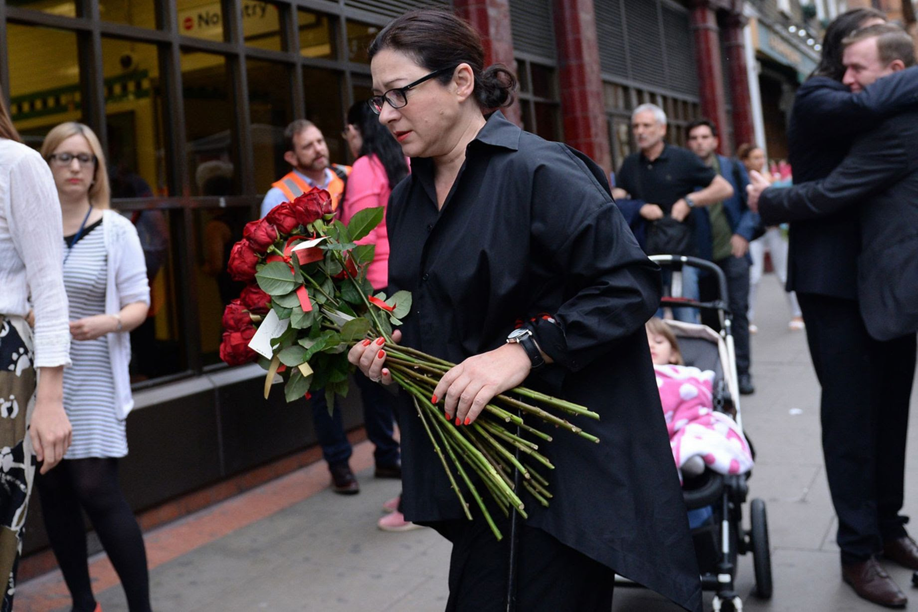 7/7 survivor Gill Hicks (centre) arrives with flowers at Russell Square tube station, London, as Britain remembers the July 7 attacks amid a welter of warnings about the enduring and changing threat from terrorism a decade on.
