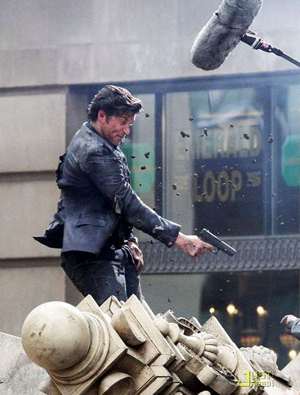 Patrick Dempsey points a gun at Shia LaBeouf (off-screen) for a scene in TRANSFORMERS 3.