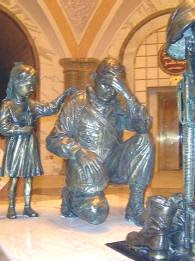 Iraqi artist Kalat was so grateful when Iraq was liberated that he made a memorial statue dedicated to the American soldier and his fallen comrades. To the left of the kneeling soldier is a small Iraqi girl giving the soldier comfort as he mourns the loss of fellow soldiers.  The statue will eventually be shipped and displayed at Fort Hood, Texas. Photo courtesy PSCM Robert A. Schultz, USCGR