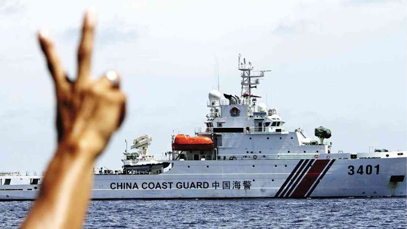 PEACE, MAN  A Philippine Marine soldier flashes the peace sign to a Chinese Coast Guard ship after it tried to block a resupply vessel from restocking the BRP Sierra Madre on Ayungin Shoal on March 29.  INQUIRER FILE PHOTO