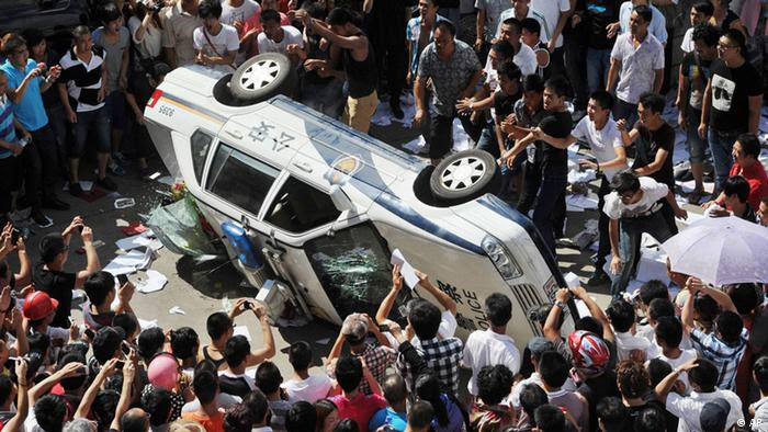 Local residents push over a police vehicle as they gather to protest against plans for a water discharge project in Qidong, China Saturday, July 28, 2012. The government in the city announced on its official website Saturday that the plans were scrapped amid opposition by local residents, who are concerned over potential pollution. (Foto:Kyodo News/AP/dapd) JAPAN OUT, MANDATORY CREDIT, NO LICENSING IN CHINA, HONG KONG, JAPAN, SOUTH KOREA AND FRANCE