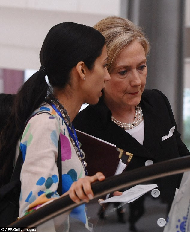 Hillary Clinton talks with Deputy Chief of Staff Huma Abedin as she takes an escalator to the meeting hall prior to the opening of the ASEAN Regional Forum on July 23, 2010