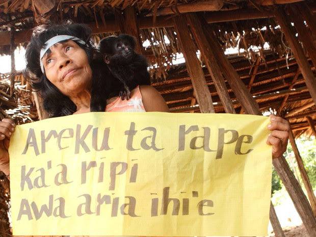 Indígena segura faixa em que está escrito 'nós existimos!' no idioma dos Awa-Guajá. O grupo, considerado um dos mais ameaçados do munso, está localizado em uma região do Maranhão muito pressionada pelo desmatamento (Foto: Eliza Capai/Greenpeace)