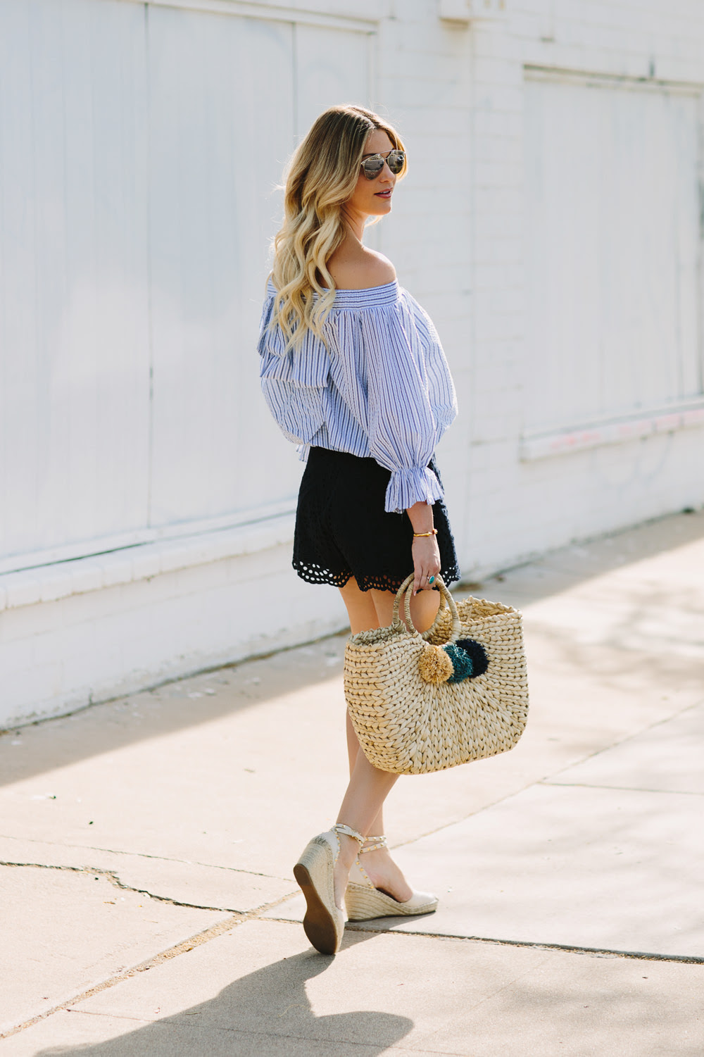 Dash of Darling styles a pastel blue Chicwish stripe off shoulder bow top with Zimmermann lace shorts and a woven beach tote for a summer outfit.