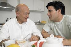 Photograph of an older man and a younger man talking at the breakfast table