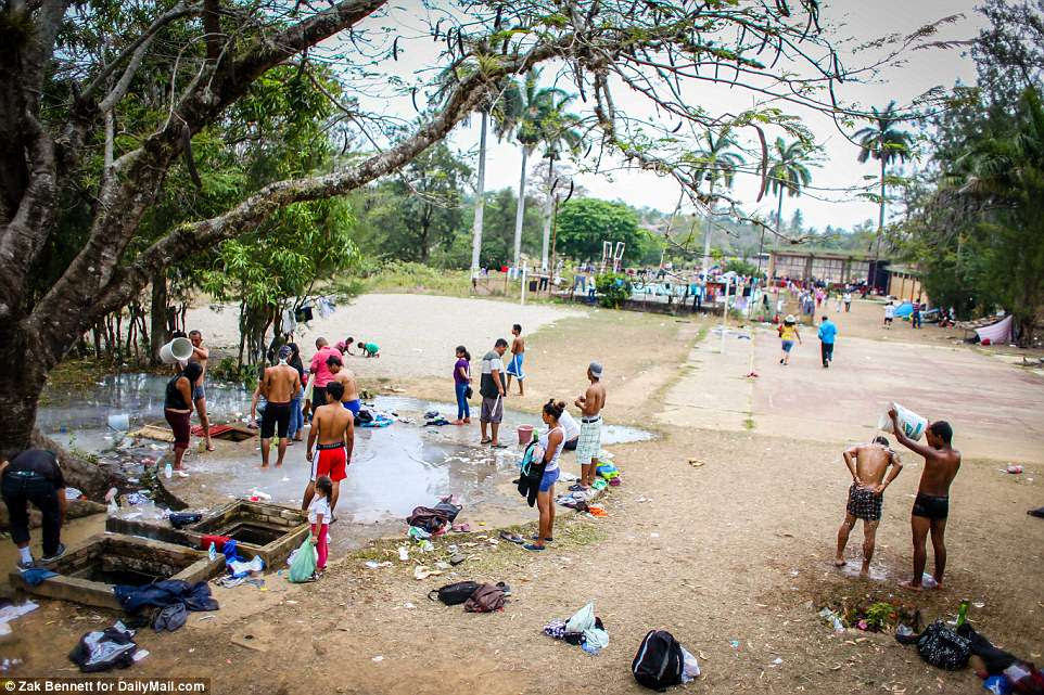 Without actual showers nearby, migrants are using large buckets to help one another shower next to a well at the Ferrocarrilero VÌctor F. Morales Sports Center