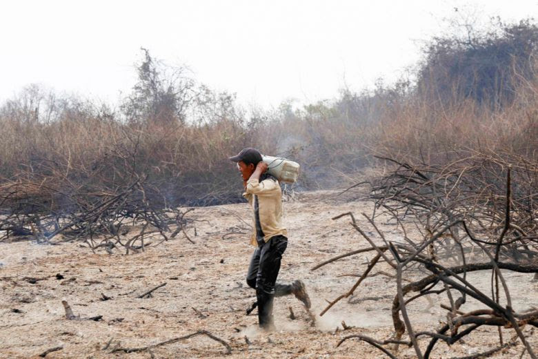 A man carries a container of water toward a fire in Battambang's Prek Toal village earlier this week in a desperate effort to control the blaze.